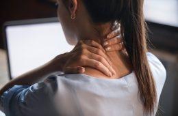 Tired woman rubbing stiff sore neck, close up rear view