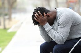 Sad depressed black man on a bench in a park