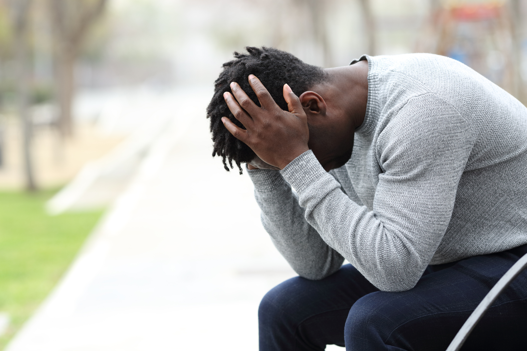 Sad depressed black man on a bench in a park | The Daily