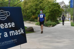 "Photo of a sign that says ""please wear a mask"" next to a path on CWRU's campus with students wearing masks walking nearby"