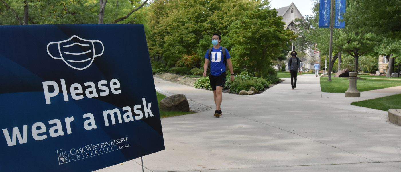 """Photo of a sign that says """"please wear a mask"""" next to a path on CWRU's campus with students wearing masks walking nearby"""