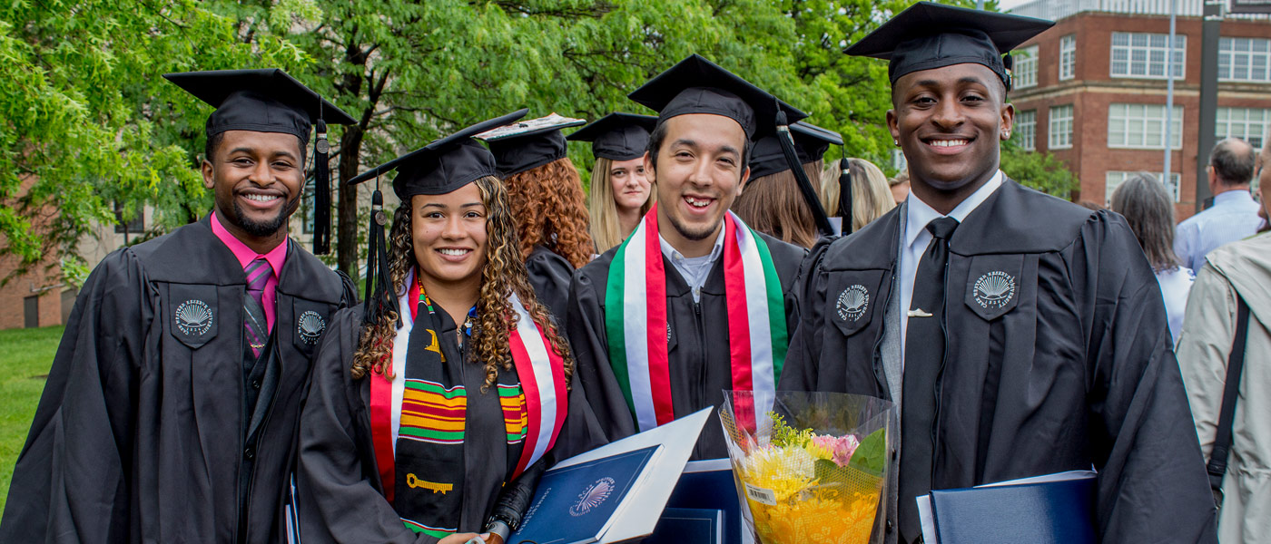 Photo of four graduates posing for a photo at commencement