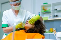 Mixed-race teenage girl with beautiful curly hair on dental checkup by middle-age caucasian woman. Coronavirus safety precaution at dentist's office.
