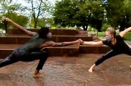 Photo of two dancers with outstretched hands holding each other on the merging fountain on campus