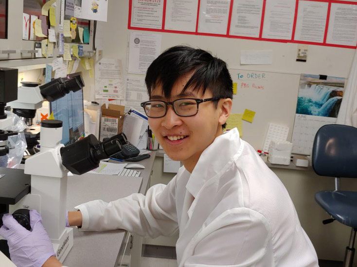 Photo of Daniel Shao smiling while posed at the bench conducting research
