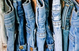 Photo showing different shades of denim blue jeans aligned closely on a rack