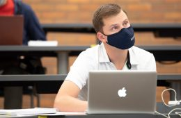 Photo of a masked student sitting a classroom with a laptop on the desk while looking up ahead
