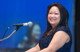 Photo of Naomi Sigg posing for a photo with a smile while standing at a podium with a microphone