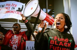 Photo from Unapologetic showing a young woman protesting while speaking into a bullhorn