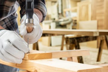Close up photo showing a man hammering a nail into a piece of wood