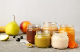 Glass jars with nutrient baby food on grey background