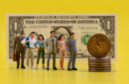 A line of multi-colored plastic various figures of people to a 1 USD coin standing on the edge in front of a 1 USD bill on a yellow background
