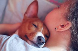 Photo of a teenager sleeping with her dog's head resting on her shoulder