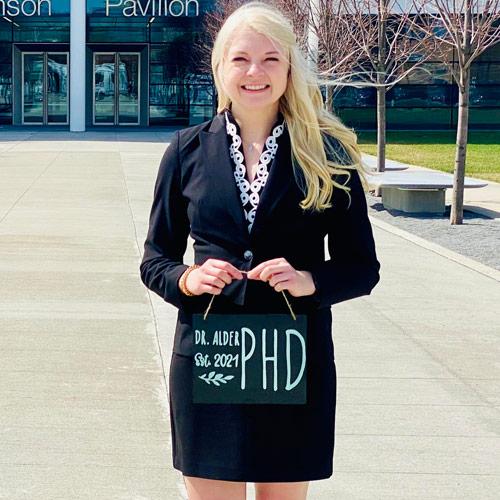 """Photo of Megan Alder holding a sign that says """"Dr. Alder est. 2021 PhD"""""""