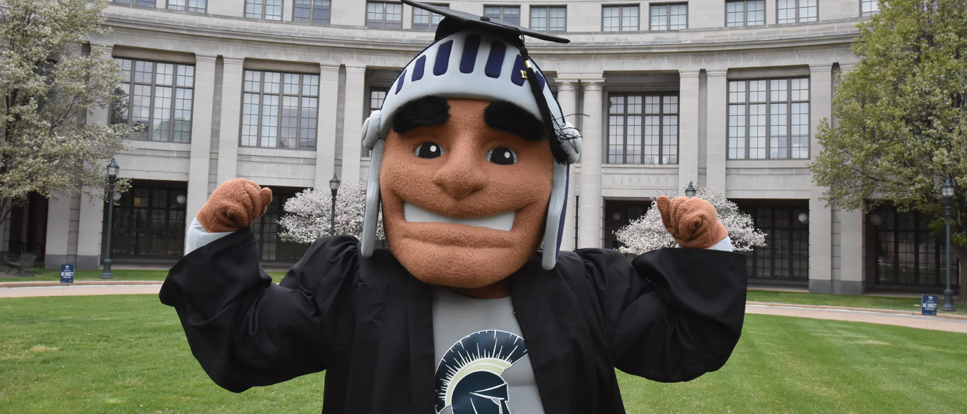 Photo of Spartie wearing a graduation cap and gown posing for a photo in front of Kelvin Smith Library