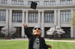 Photo of Spartie mascot wearing a graduation gown and tossing a cap in the air in front of Kelvin Smith Library