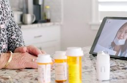 Photo of a patient in a video call with a nurse on a tablet with prescription bottles on the counter