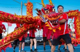 Photo of Wayne Wong holding the head of a dragon puppet during a festival dance