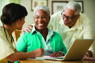 African American elderly couple in front of a laptop