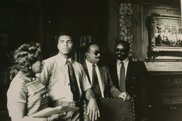 Black and white photo of Muhammad Ali visiting the Hanna Lounge as others stand nearby him