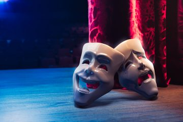 Theater masks in front of a red curtain/ 3D rendering