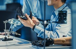 Technological Prosthetic Robot Arm is Tested by Two Professional Development Engineers in a High Tech Research Laboratory with Modern Futuristic Equipment. Compare Data on a Personal Computer.