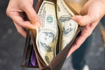 Young woman traveler saving and spending money on holidays trip