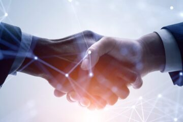 Photo showing two people shaking hands with connected points laying over top to represent digital concepts
