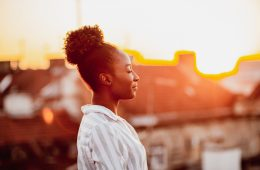 Young African American woman is relaxing on the rooftop