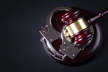 Wooden judge gavel and police handcuffs isolated on black background
