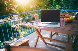 Laptop on a wooden table on a sunny summer terrace, summer mood and vacation in a country house.