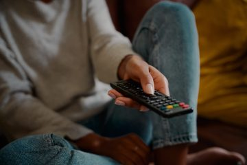 Woman hand holding television remote at home