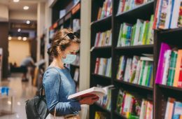 Woman choosing a new book in the bookstore during COVID-19 pandemic
