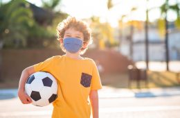 Child with facial tissue protection mask with soccer ball outdoors during pandemic