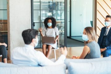 Business people on a meeting keeping distance and wearing face protective masks while discussing