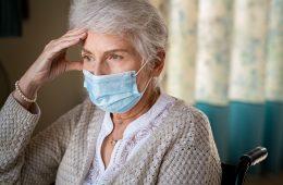 Sad senior woman in wheelchair wearing face mask