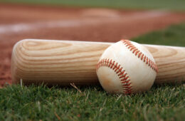Close-up if baseball and bat resting on the field