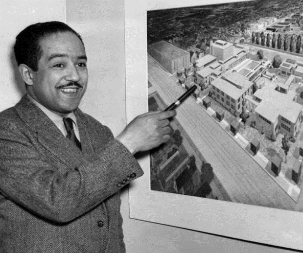 Black and white photo of playwright Langston Hughes pointing to a photo on the wall of buildings in a neighborhood