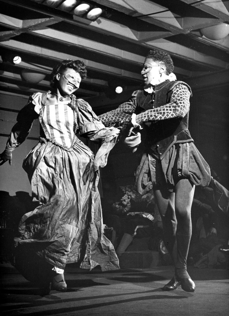Black and white photo of two costumed actors dancing on stage and wearing masks at Karamu House