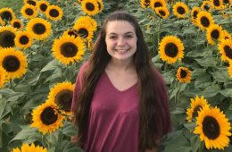 Photo of Alex Welsh standing in a field of sunflowers