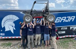 Photo of CWRU Motorsports team hoisting vehicle up in the air
