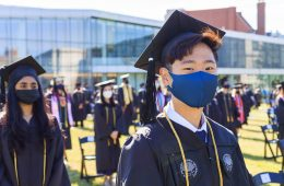 Photo of a CWRU graduate wearing a mask and looking ahead during commencement ceremonies with other graduates surrounding them
