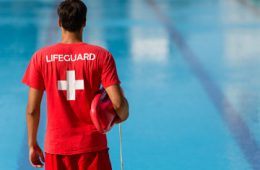 """Photo of a lifeguard looking at a pool from behind wearing all read and a T-shirt that reads """"lifeguard"""" and holding a floatation device"""