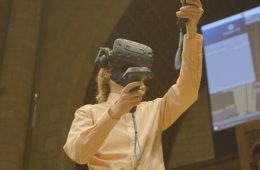 Photo of a student using a VR headset and controllers on the Maltz Performing Arts Center stage
