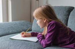 A girl is lying on a couch and is writing with a pencil on paper notes