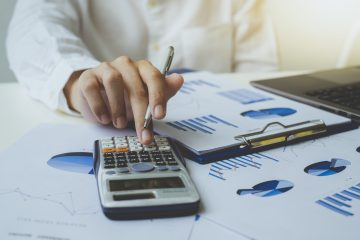 Close up of businessman or accountant hand holding pen working on calculator to calculate the number, graph chart, and business data. Accountancy documents and business information on the desk at the office, Business concept.