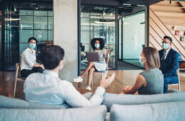 Group of entrepreneurs, wearing masks, sitting at a distance in the office and talking