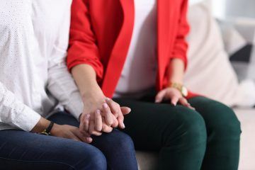 Two women tightly holding hands on couch at home close-up