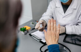 Patient refusing the coronavirus vaccine offered by doctor