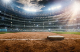 A wide angle of a outdoor baseball stadium full of spectators under a stormy night sky. The base is seen. The image has depth of field with the focus on the foreground part of the pitch. Stadium and all elements are made in 3D.